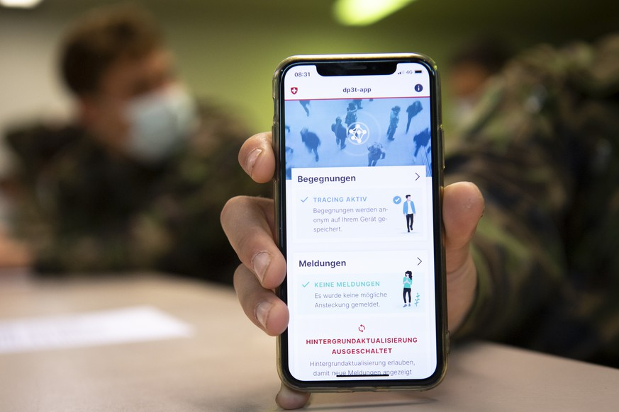 Soldier of the Swiss army wearing protective face mask looking at a smartphone with the app using Decentralized Privacy-Preserving Proximity Tracing (DP-3T) during a test, with 100 soldiers, during the state of emergency of the coronavirus disease (COVID-19) outbreak, in the military compound of Chamblon near Yverdon-les-bains, Switzerland, Thursday, April 30, 2020. Secure contact tracing could be a powerful tool to fight the spread of COVID-19. A unique, decentralized system developed as part of an international consortium, including Swiss Federal Institute of Technology, EPFL Lausanne and ETH Zurich, will soon be launched with the support of the Swiss Federal Office of Public Health. DP-3T proposes a secure, decentralized, privacy-preserving proximity tracing system based on the Bluetooth Low Energy standard. Its goal is to simplify and accelerate the process of identifying people who have been in contact with someone infected with the SARS-CoV-2 virus. (KEYSTONE/Laurent Gillieron)
